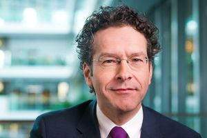 The Dutch Minister of Finance tries to balance policing as ESM President abroad and handling a sinking economy at home.
