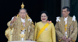 Thai King Bhumibol Adulyadej waves as his wife Queen Sirikit and son Vajiralongkorn look on on his 80th birthday at the Grand Palace in Bangkok